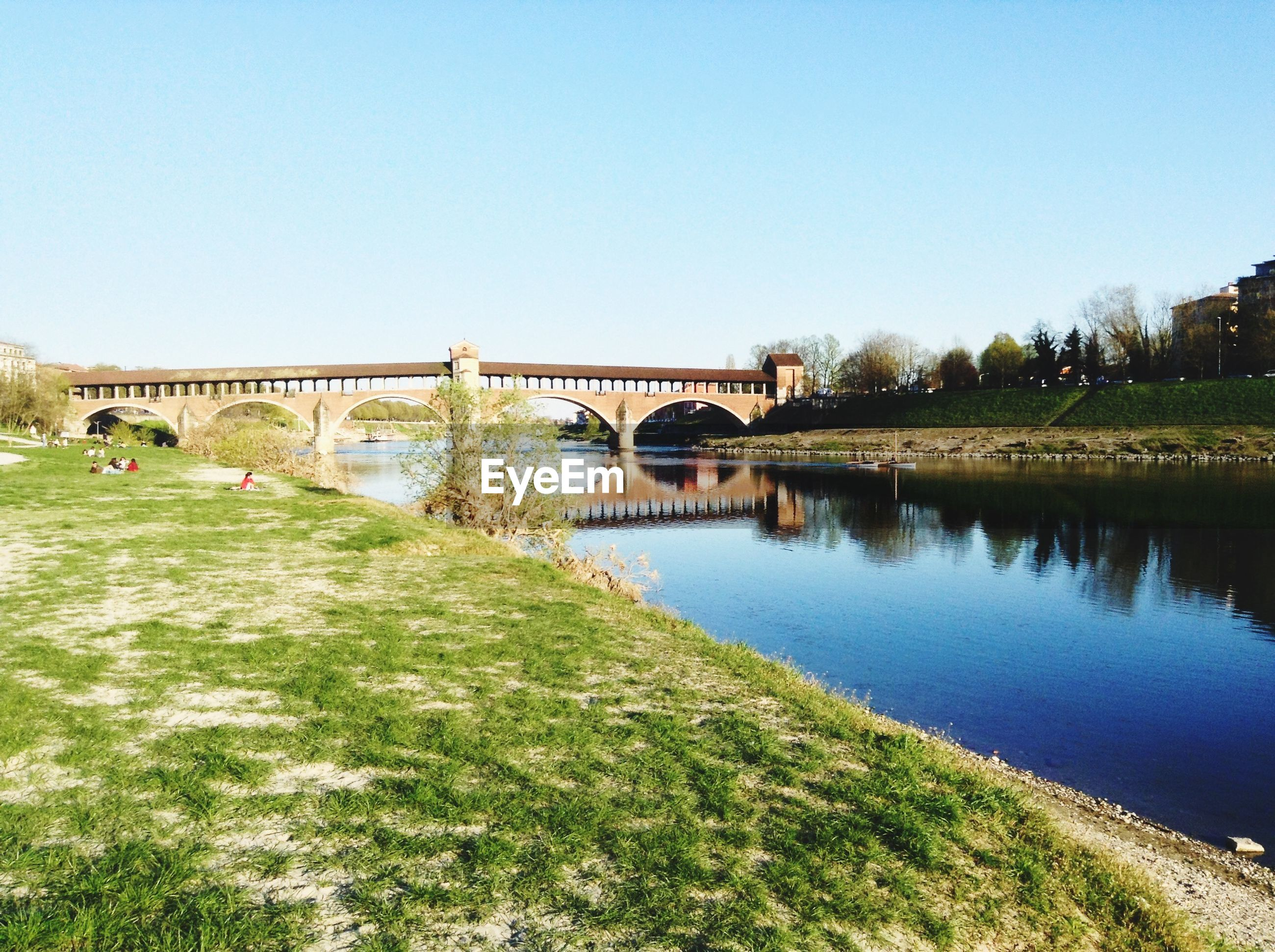 Arch bridge over river against clear sky