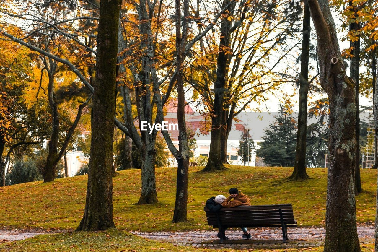 WOMAN SITTING ON BENCH IN PARK DURING AUTUMN