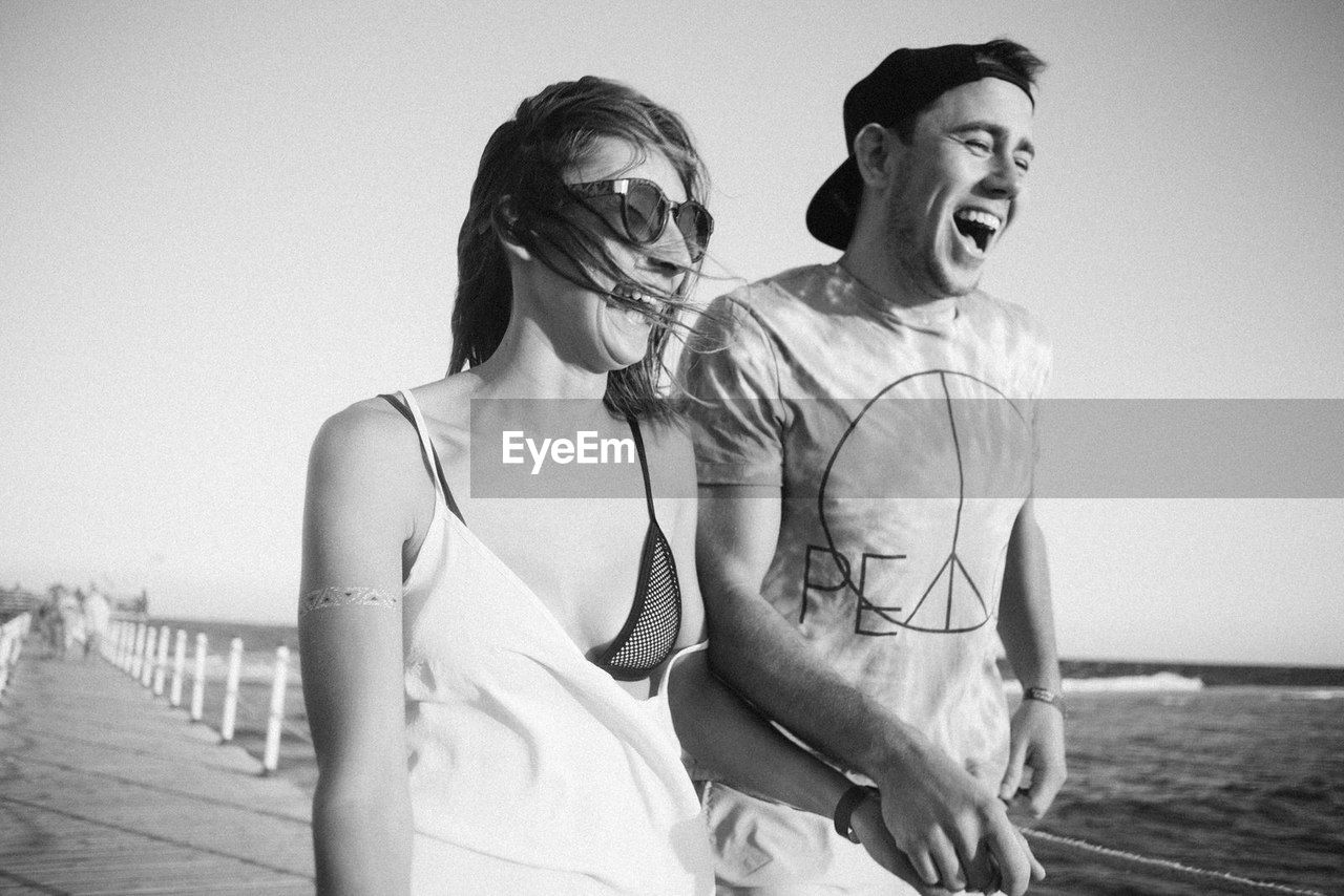 two people, real people, leisure activity, young women, beach, young adult, sea, togetherness, mouth open, fun, casual clothing, lifestyles, happiness, outdoors, sand, love, water, young men, smiling, couple - relationship, bonding, day, sky, friendship, horizon over water, nature