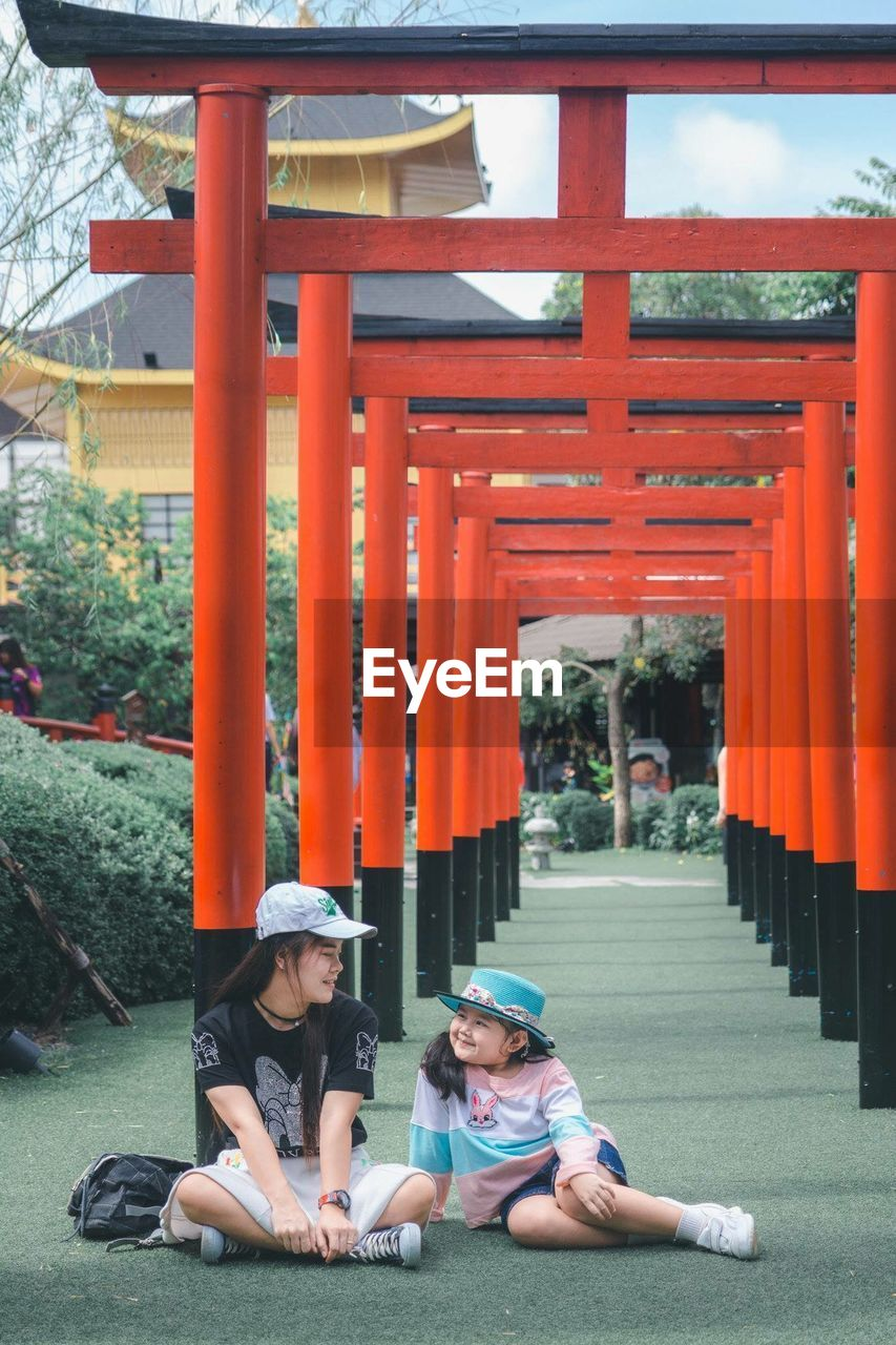 Full length of mother sitting with daughter by torii gate