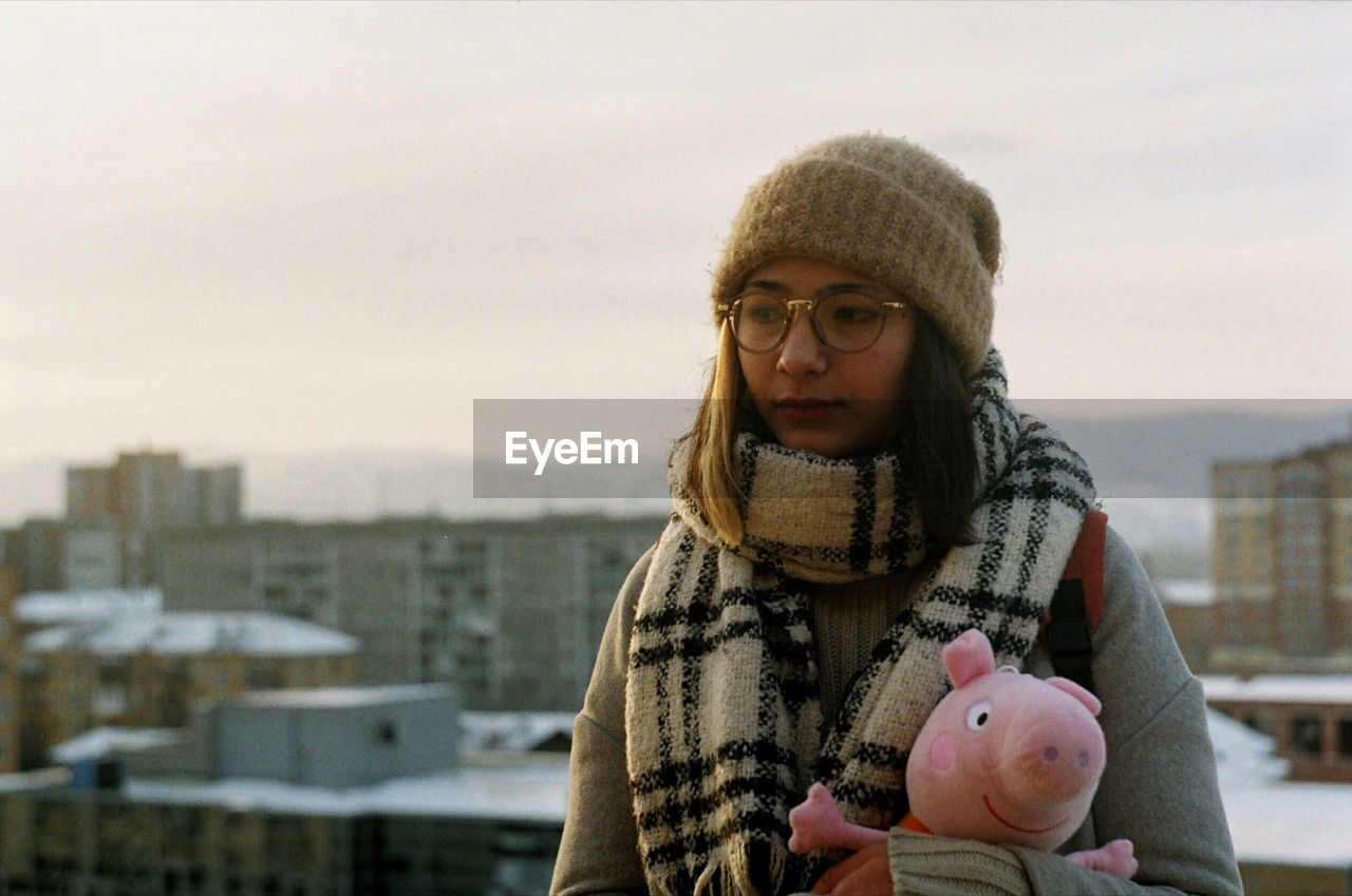Woman With Stuffed Toy In City Against Sky During Winter
