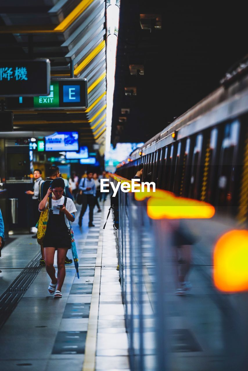 real people, architecture, illuminated, walking, transportation, public transportation, lifestyles, women, built structure, motion, travel, railroad station, people, mode of transportation, rail transportation, incidental people, railroad station platform, night, full length, rear view