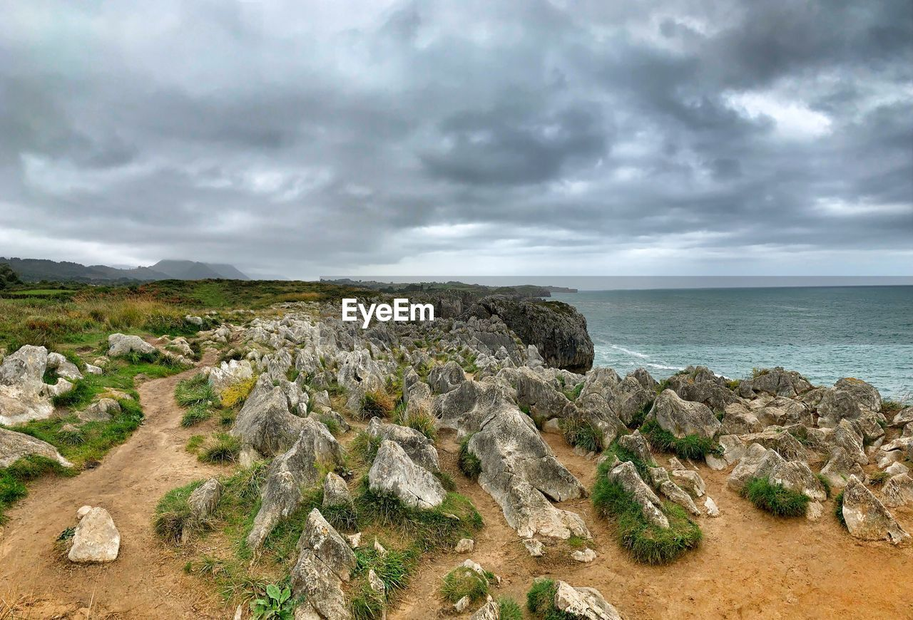 sky, cloud - sky, sea, land, beauty in nature, scenics - nature, water, nature, rock, overcast, tranquil scene, no people, horizon, tranquility, beach, non-urban scene, environment, rock - object, outdoors, horizon over water