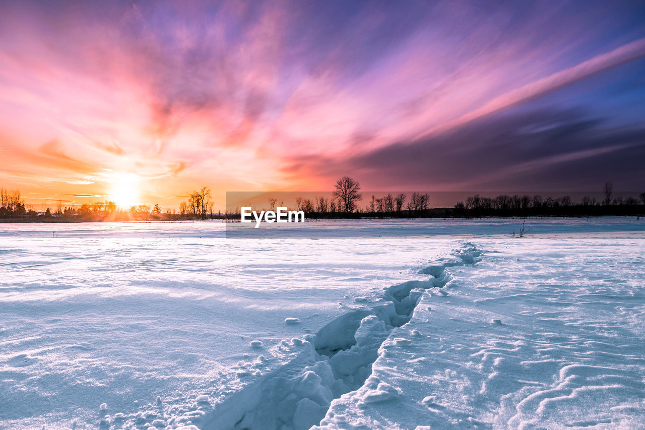 sky, winter, sunset, cold temperature, snow, beauty in nature, scenics - nature, cloud - sky, frozen, tranquil scene, nature, tranquility, water, ice, orange color, no people, non-urban scene, environment, covering, outdoors, cold