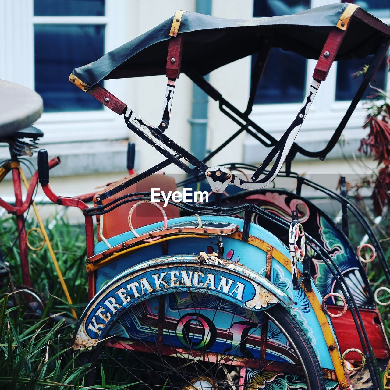 transportation, mode of transportation, day, no people, focus on foreground, close-up, multi colored, outdoors, land vehicle, communication, metal, nature, nautical vessel, design, number, bicycle, shape, seat, text, architecture, wheel