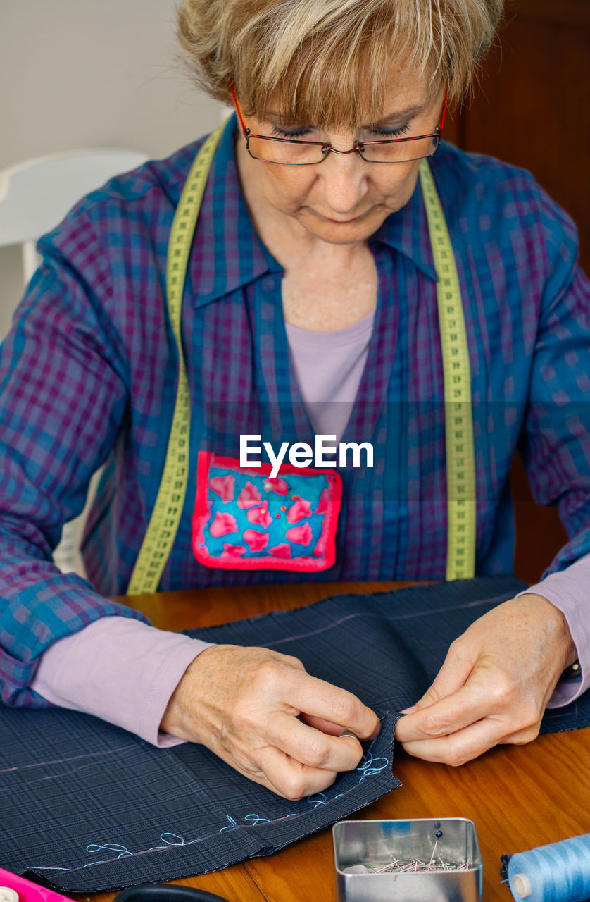 Woman working over fabric on table