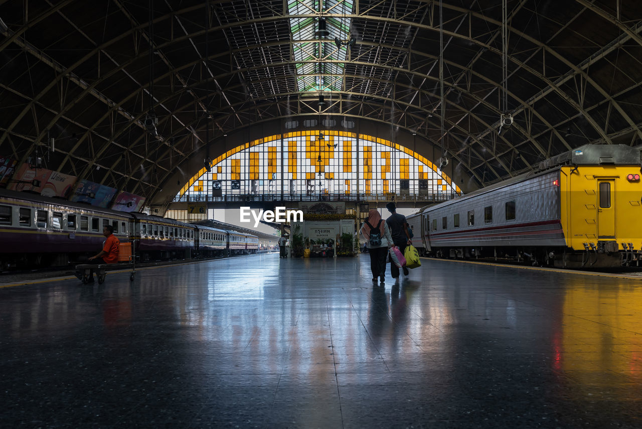 transportation, architecture, mode of transportation, travel, built structure, public transportation, real people, rail transportation, railroad station, train, group of people, men, people, arch, lifestyles, train - vehicle, city, journey, women, indoors, rain