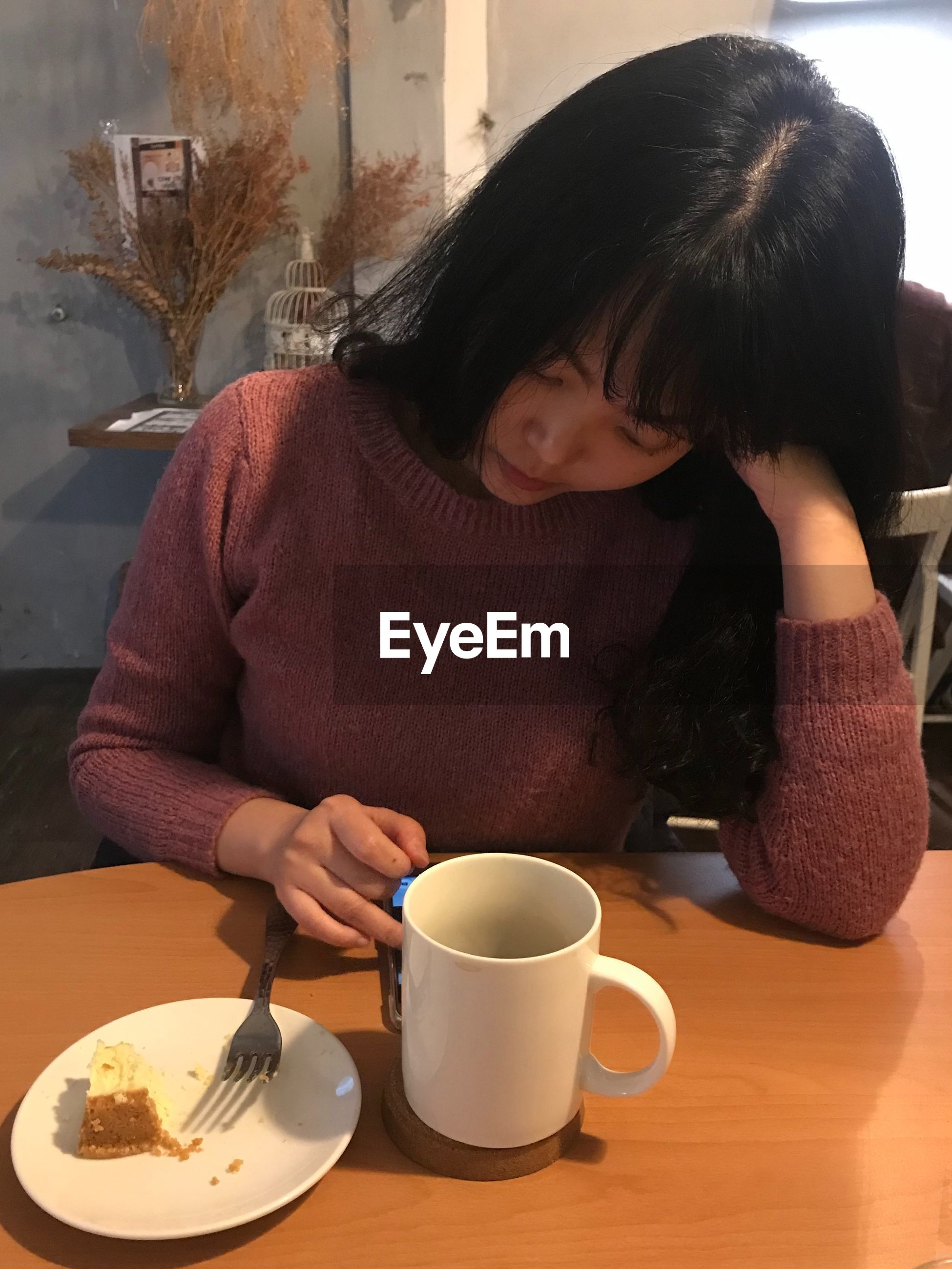 High angle view of woman using phone in cafe