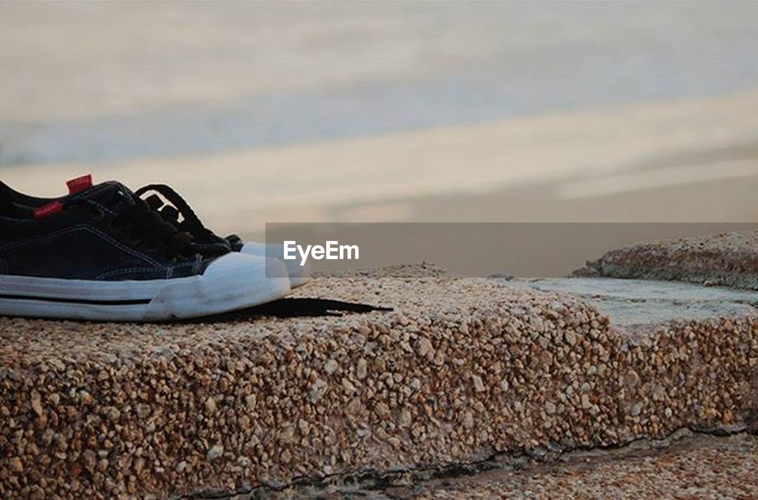 beach, sand, shore, sea, focus on foreground, sky, day, water, shoe, outdoors, rock - object, lifestyles, nature, stone - object, close-up, pebble, leisure activity, transportation