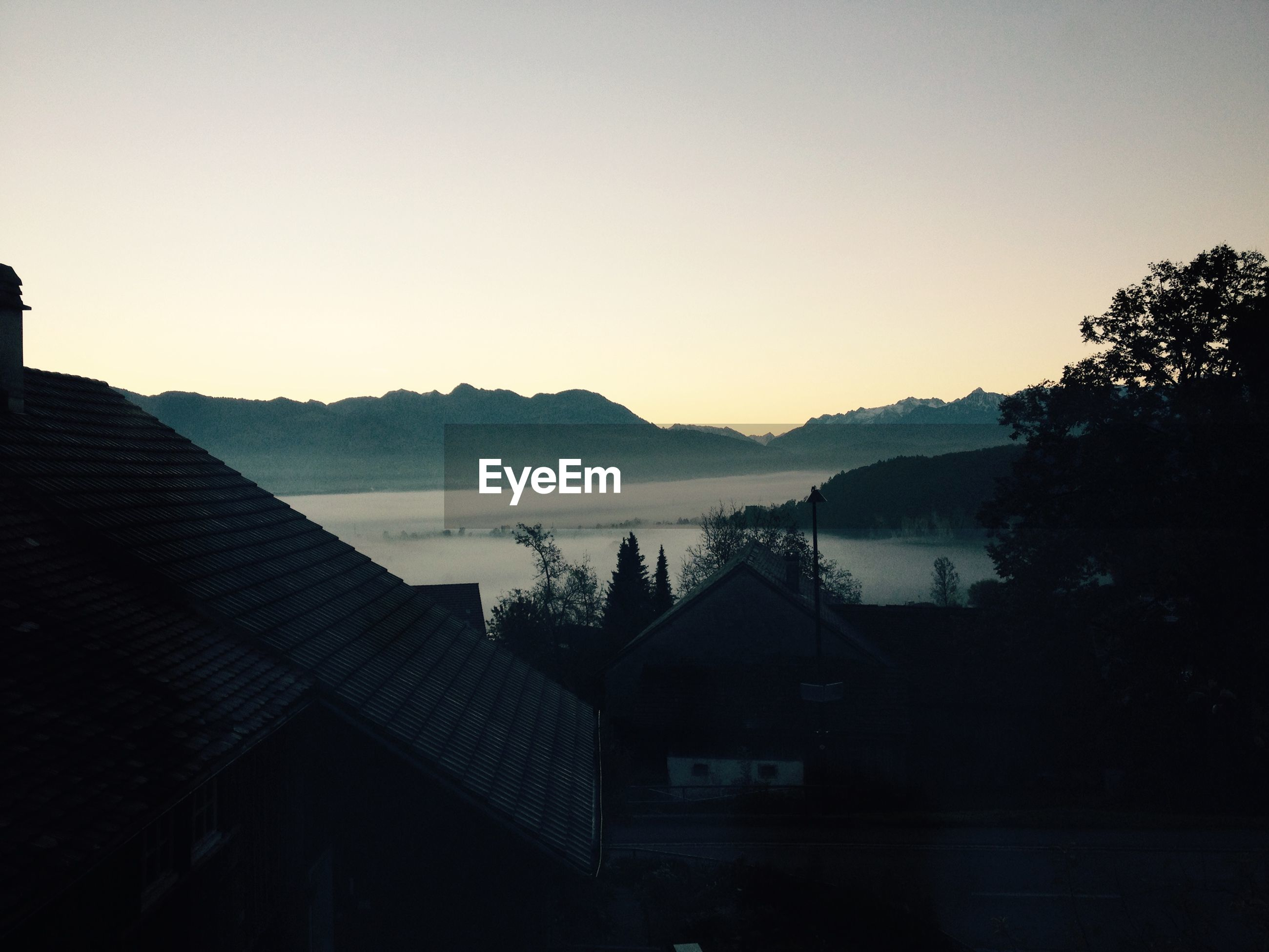 clear sky, copy space, building exterior, built structure, mountain, architecture, scenics, house, tranquil scene, tree, sunset, tranquility, silhouette, water, nature, beauty in nature, lake, mountain range, residential structure