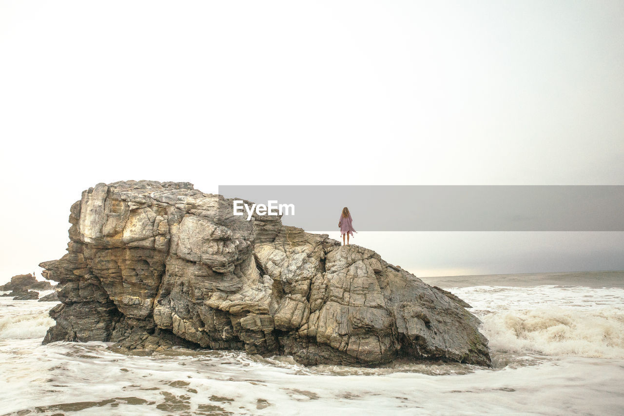 Woman standing on rock formations at beach against clear sky