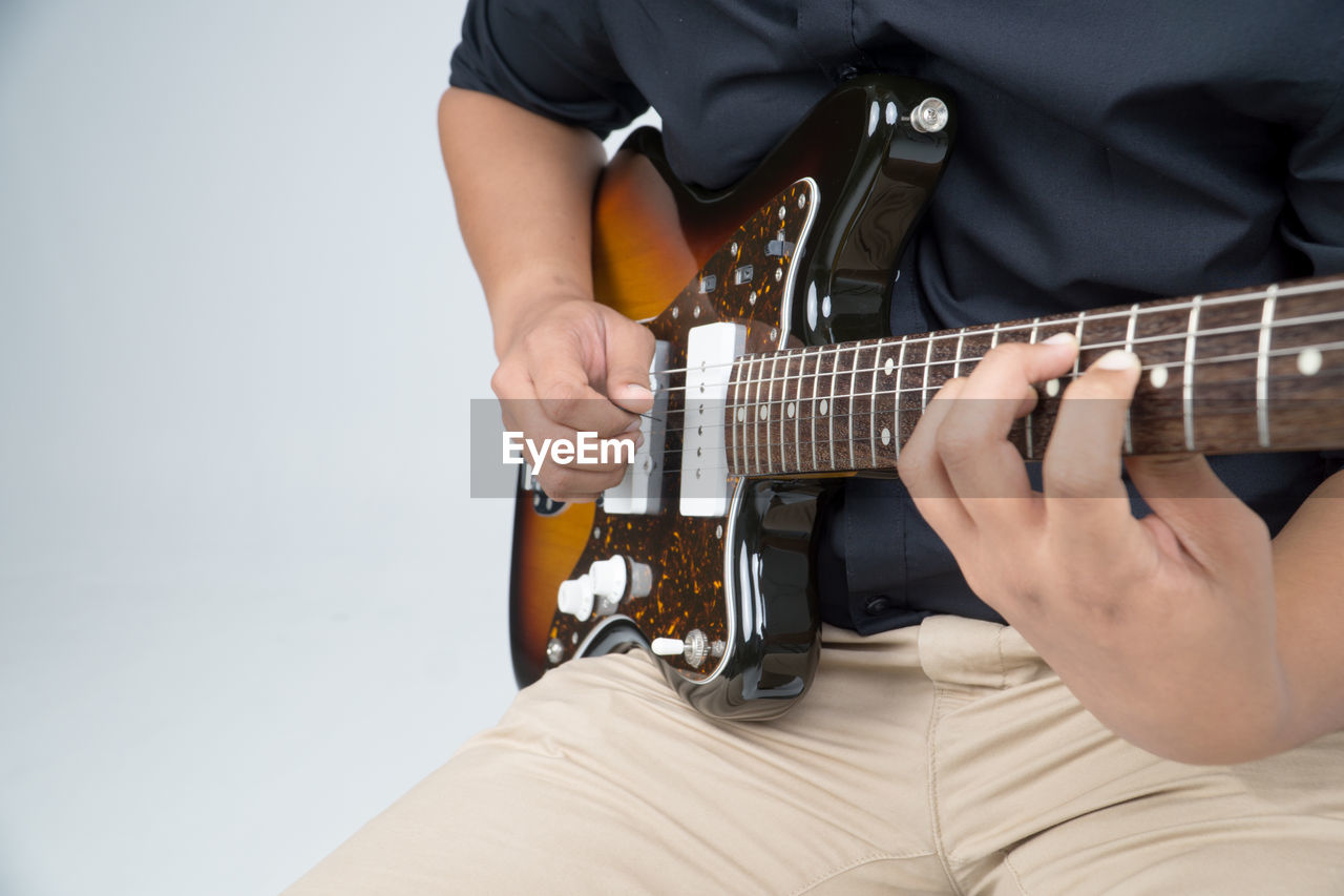 Midsection Of Musician Playing Guitar Against White Background
