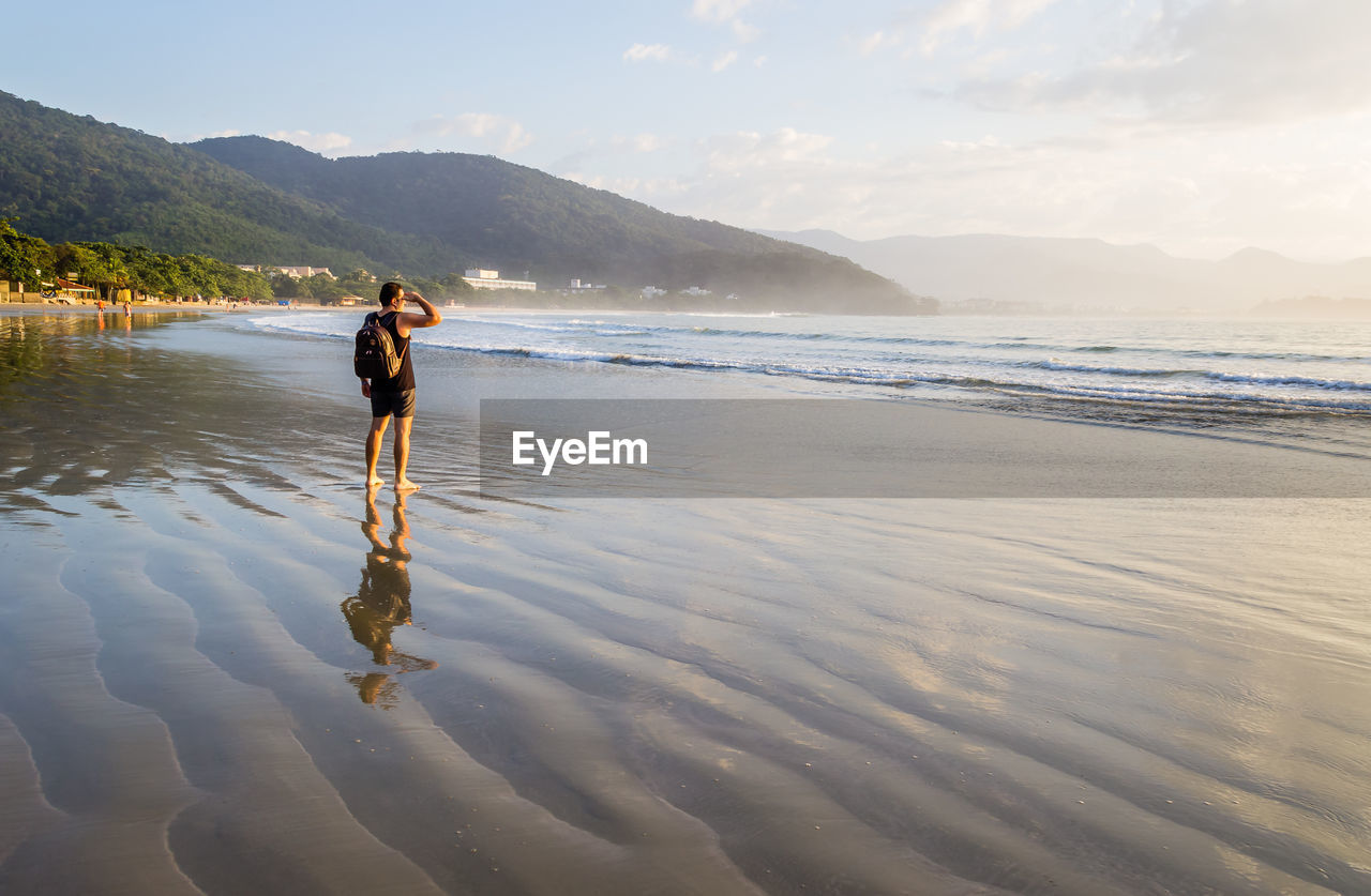 Full length of man standing at beach against sky