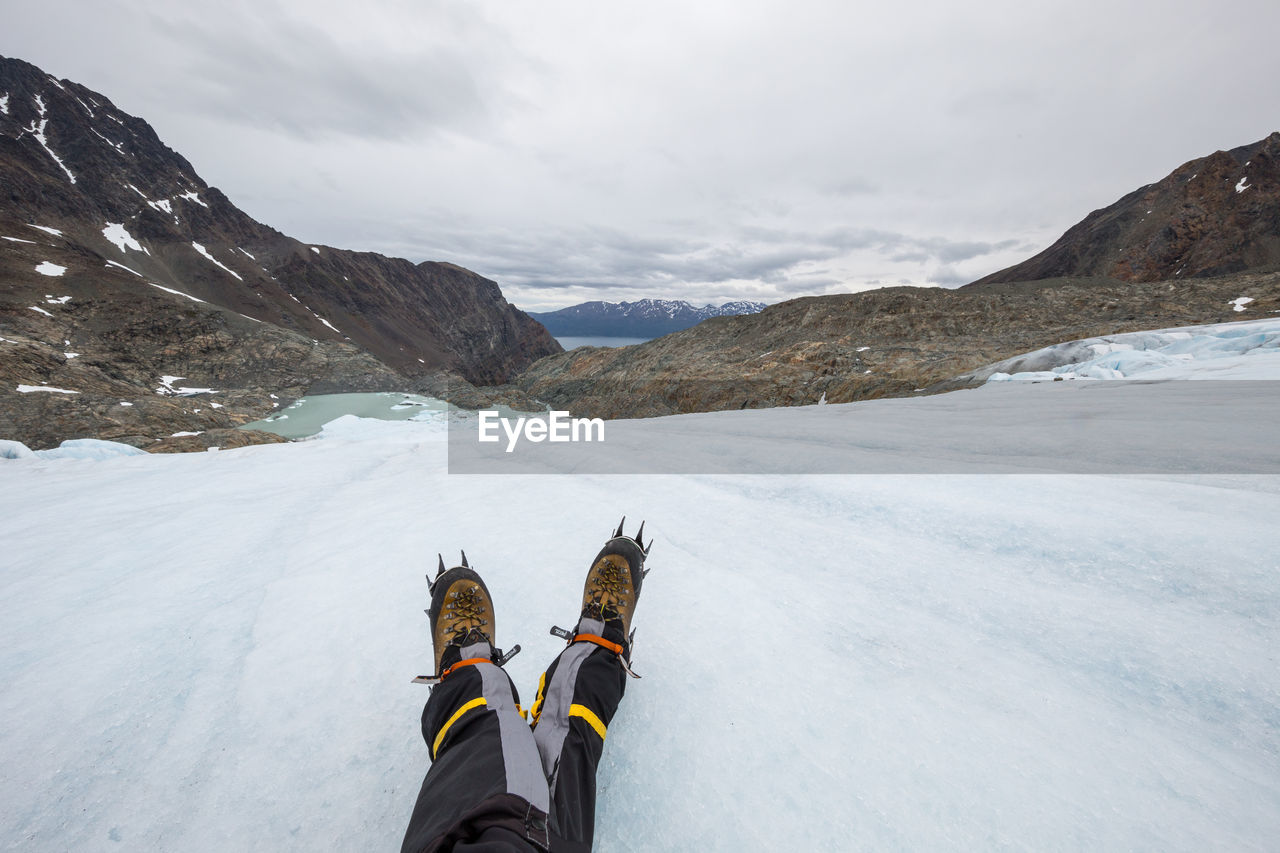 Low section of person wearing snow boots on snow covered mountains against cloudy sky