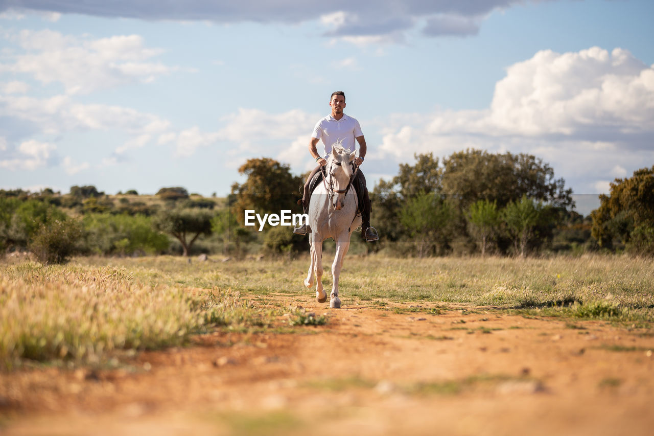 Man riding horse on land against sky