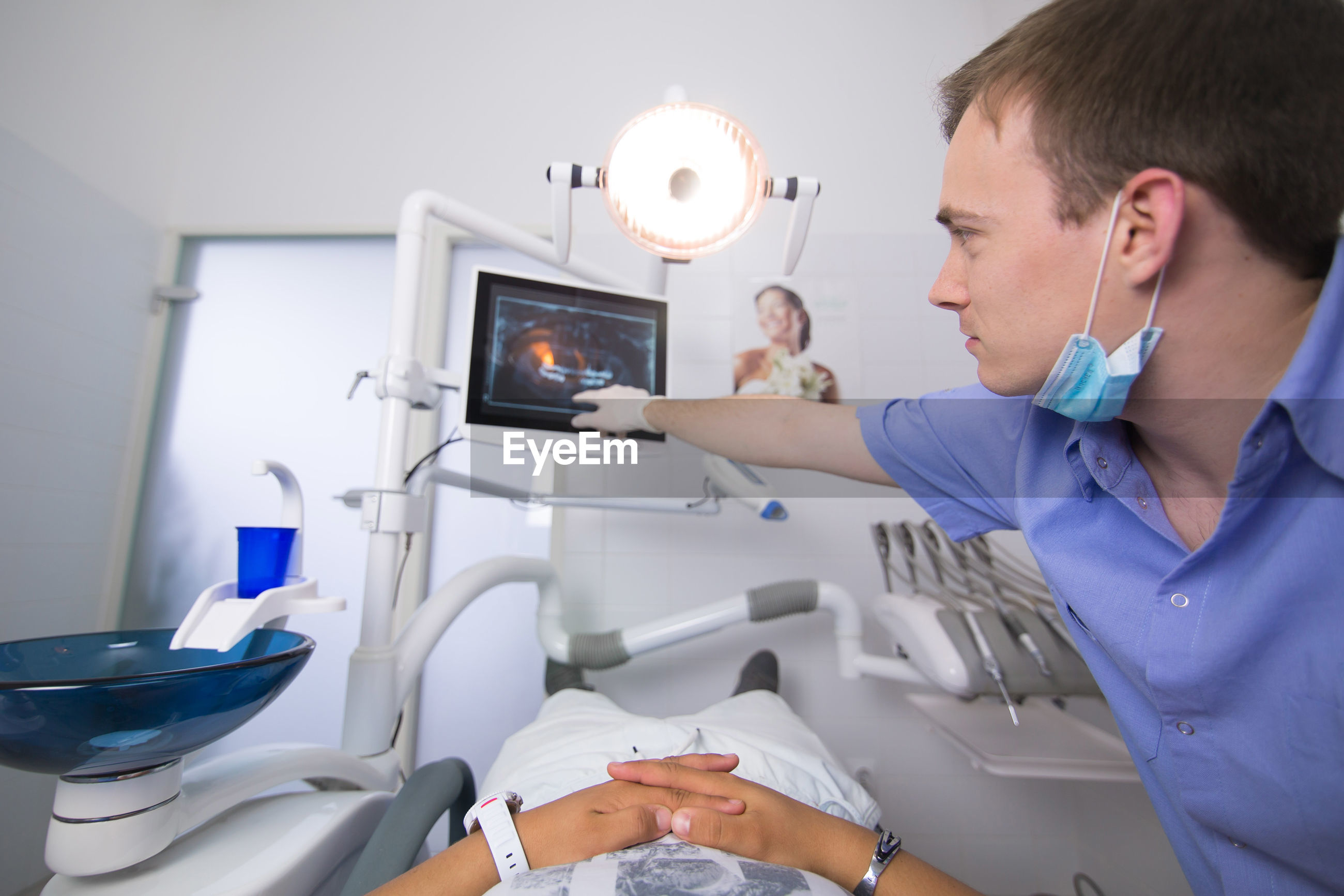 Doctor pointing at monitor with patient lying down at dentist office
