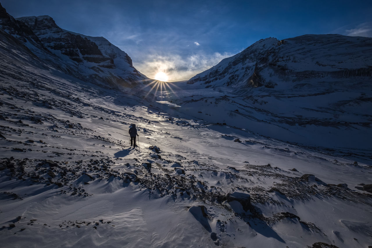 One Person Hiking On Snowy Mountains Against Sky