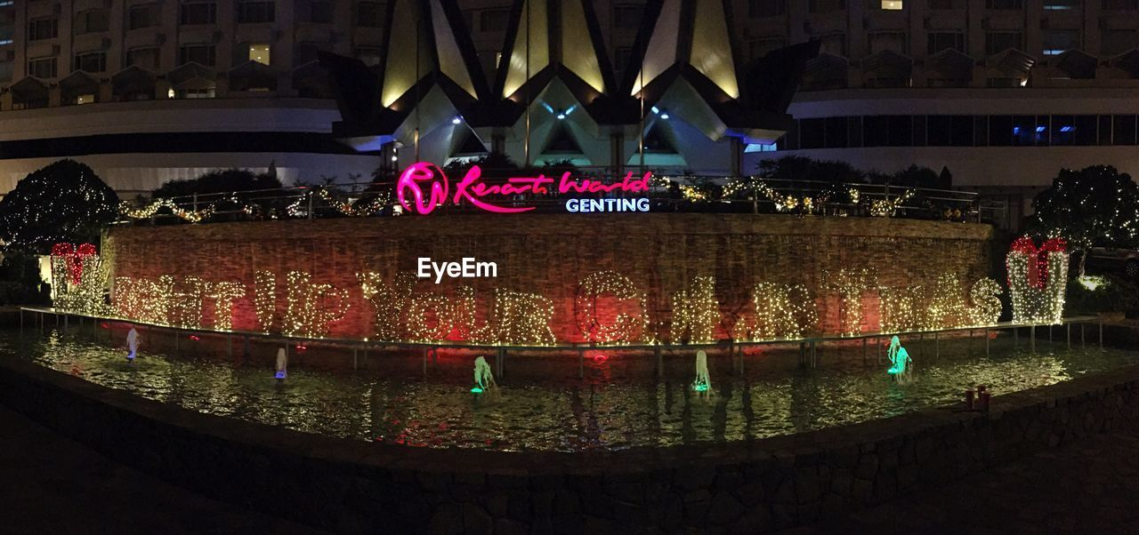 text, architecture, illuminated, night, built structure, celebration, communication, building exterior, large group of people, outdoors