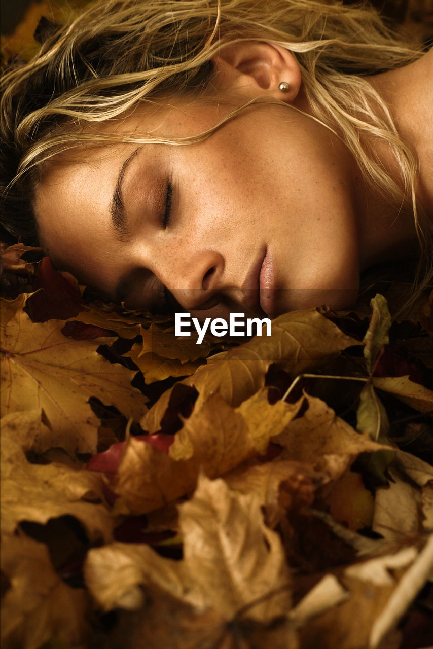 Close-up of young woman lying down on autumn leaves