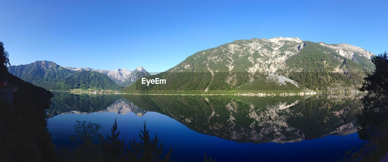 sky, tranquility, tranquil scene, mountain, scenics - nature, beauty in nature, water, blue, reflection, lake, waterfront, idyllic, clear sky, nature, non-urban scene, symmetry, day, mountain range, copy space, no people, outdoors, formation, mountain peak