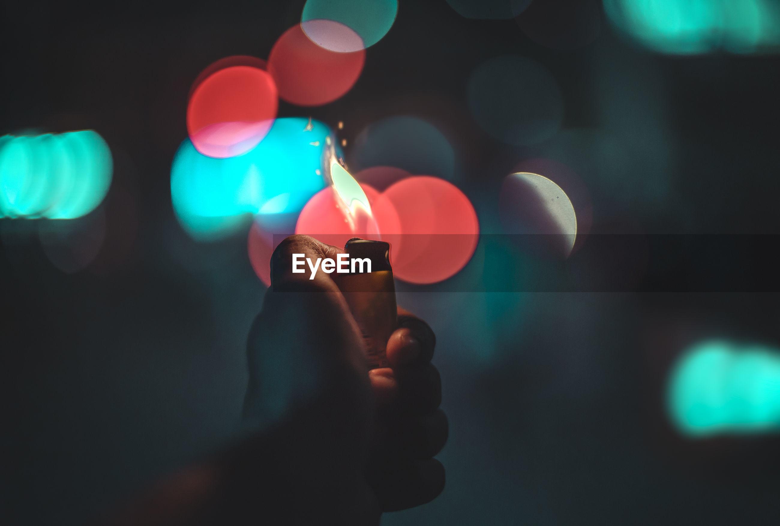 Close-up of human hand holding illuminated cigarette lighter against illuminated lights