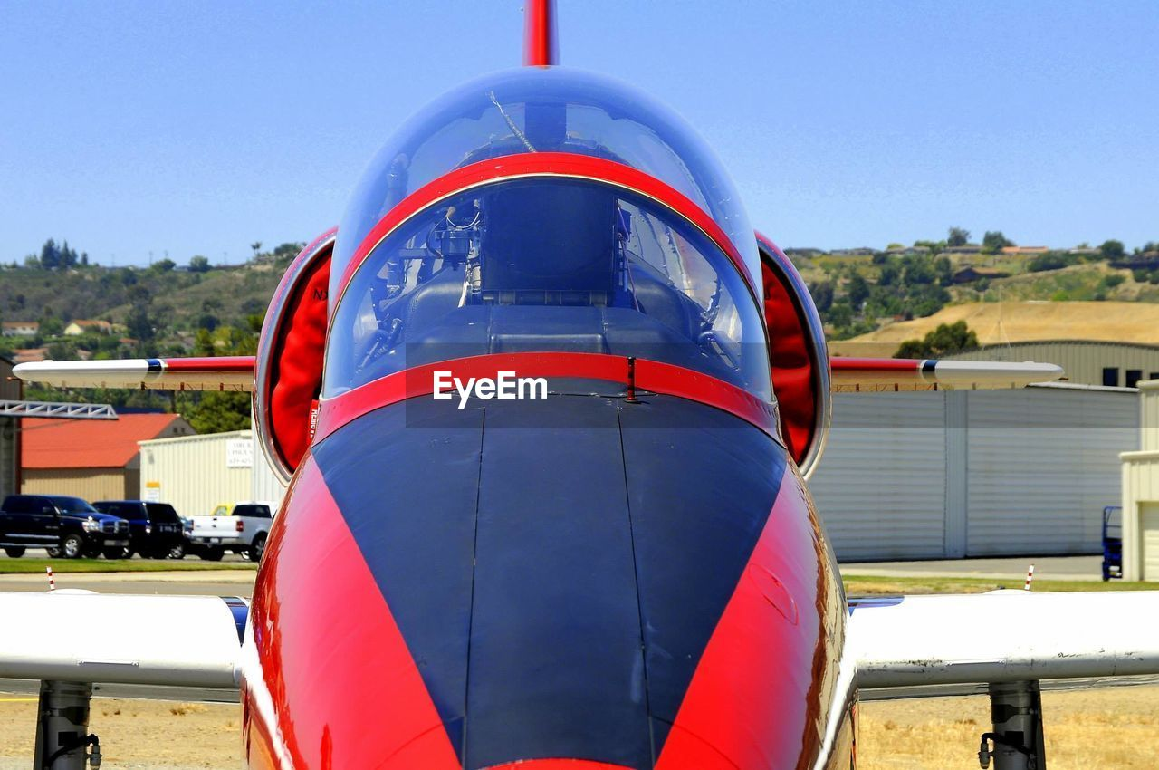 red, transportation, air vehicle, day, airplane, blue, no people, airport, outdoors, built structure, close-up, sky, architecture