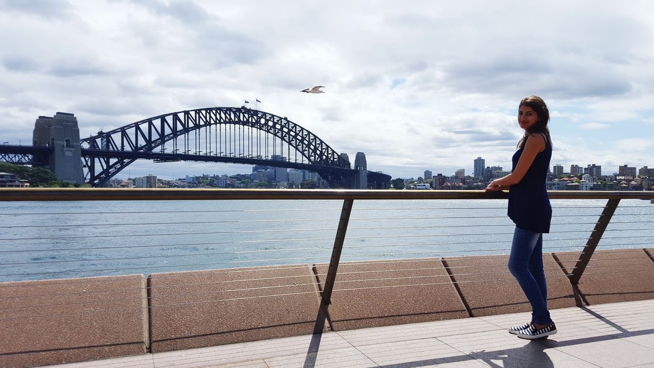 Side View Full Length Of Young Woman With Sydney Harbor Bridge Over Parramatta River In City