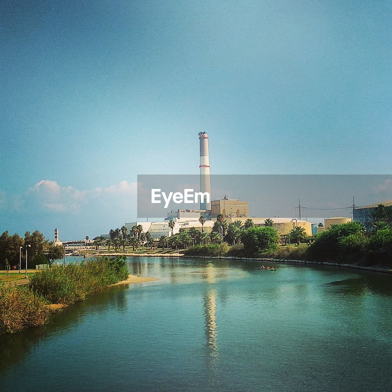 built structure, industry, architecture, smoke stack, building exterior, factory, no people, water, sky, day, blue, outdoors, tree, clear sky, power station