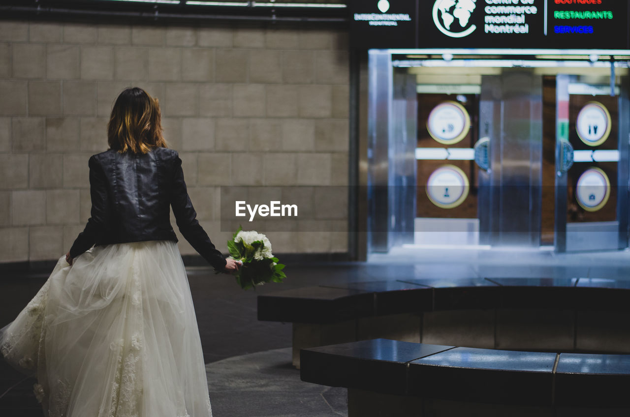 Rear View Of Bride Holding Bouquet In Subway