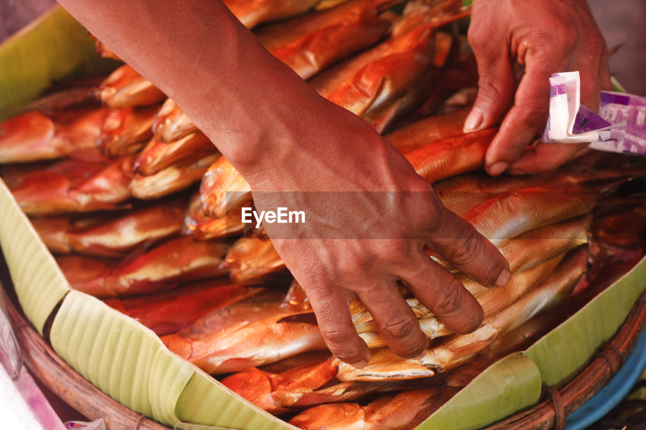 Cropped hands of man arranging fishes in basket