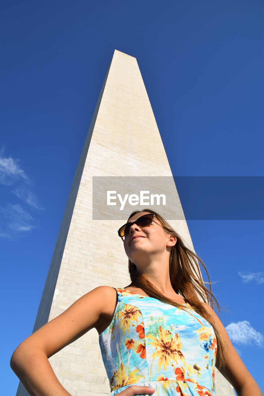 Low Angle View Of Woman Standing By Washington Monument Against Sky