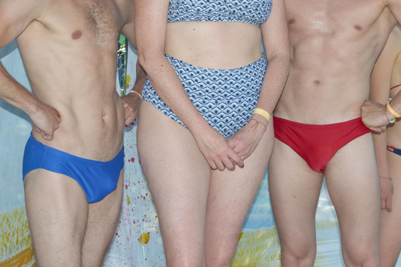 Midsection Of Shirtless Men Standing By Woman Wearing Bikini