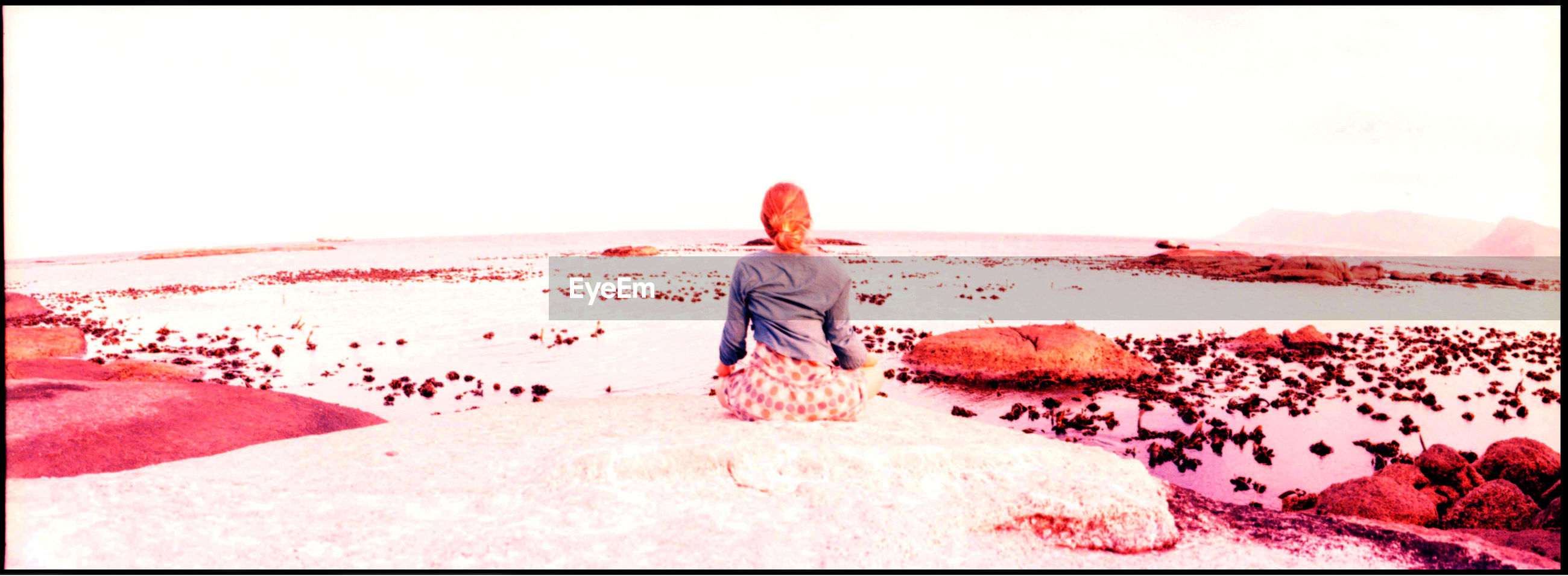 Rear view of woman sitting on rocks in front of river against clear sky