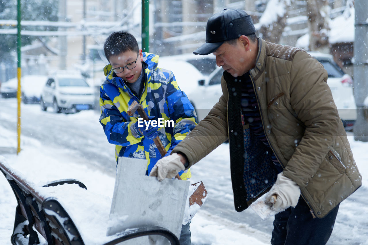 winter, two people, men, cold temperature, clothing, three quarter length, real people, snow, males, day, transportation, city, adult, mode of transportation, bicycle, warm clothing, leisure activity, incidental people, mature men, outdoors