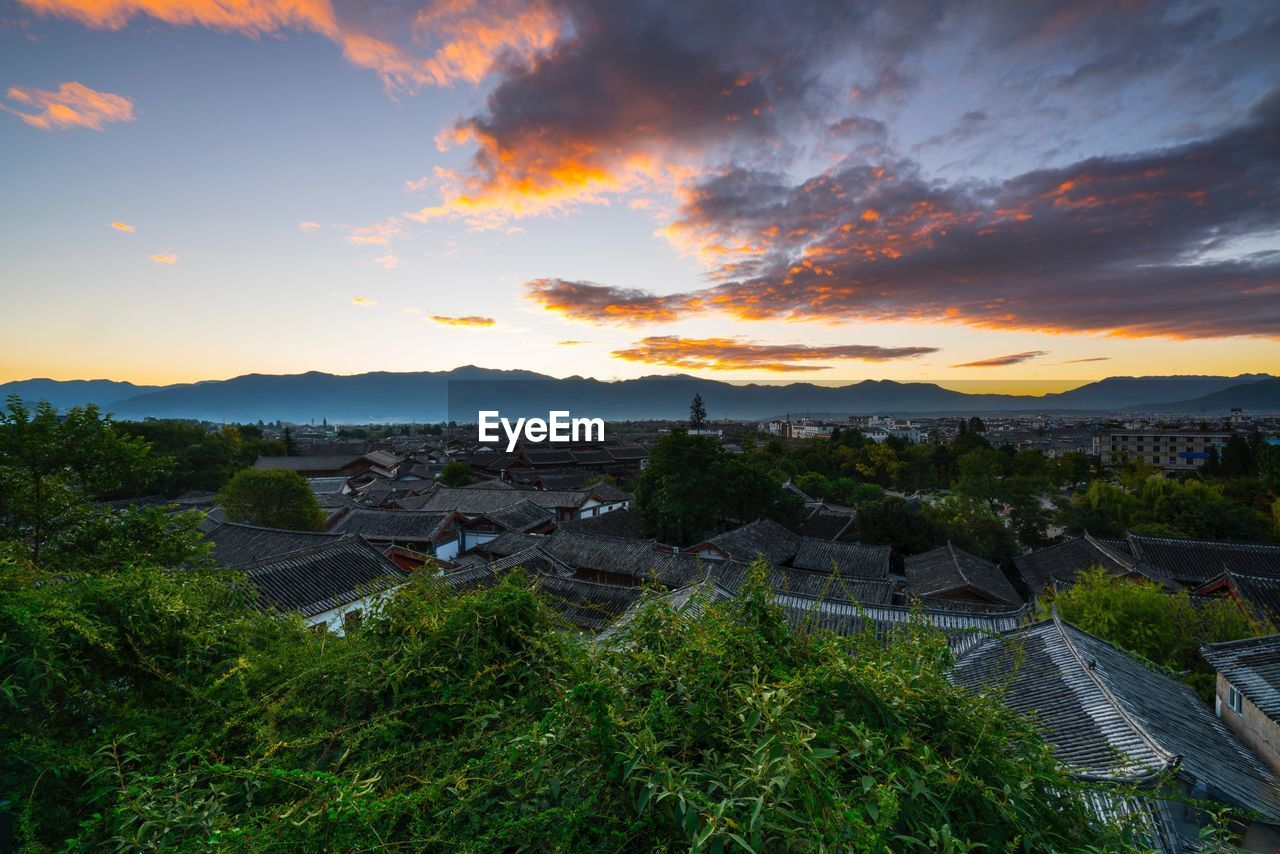 architecture, built structure, sunset, high angle view, sky, no people, beauty in nature, building exterior, outdoors, nature, scenics, tree, mountain, cityscape, day