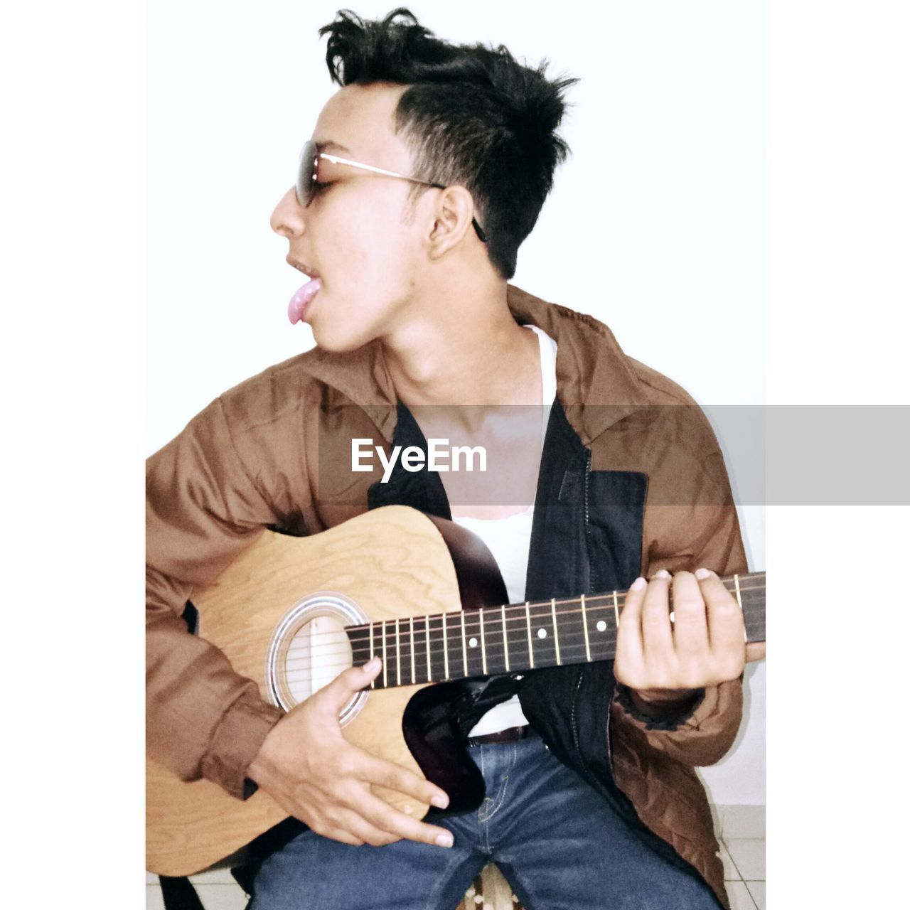 Young man sticking out tongue  while playing guitar against white background
