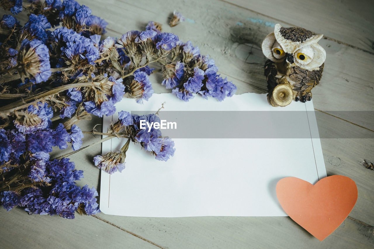 High angle view of flowers with paper on table