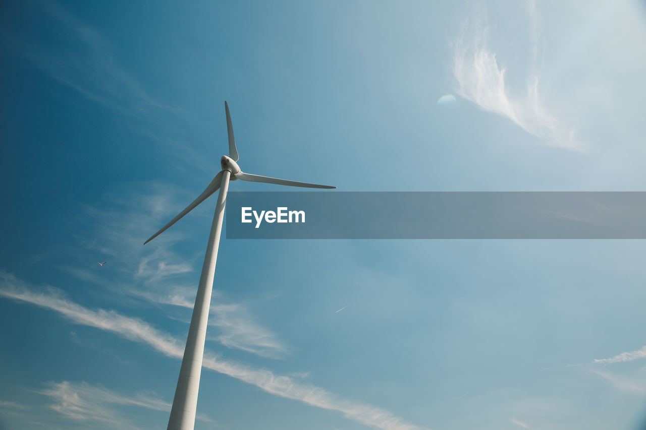 Low Angle View Of Wind Turbine Against Blue Sky