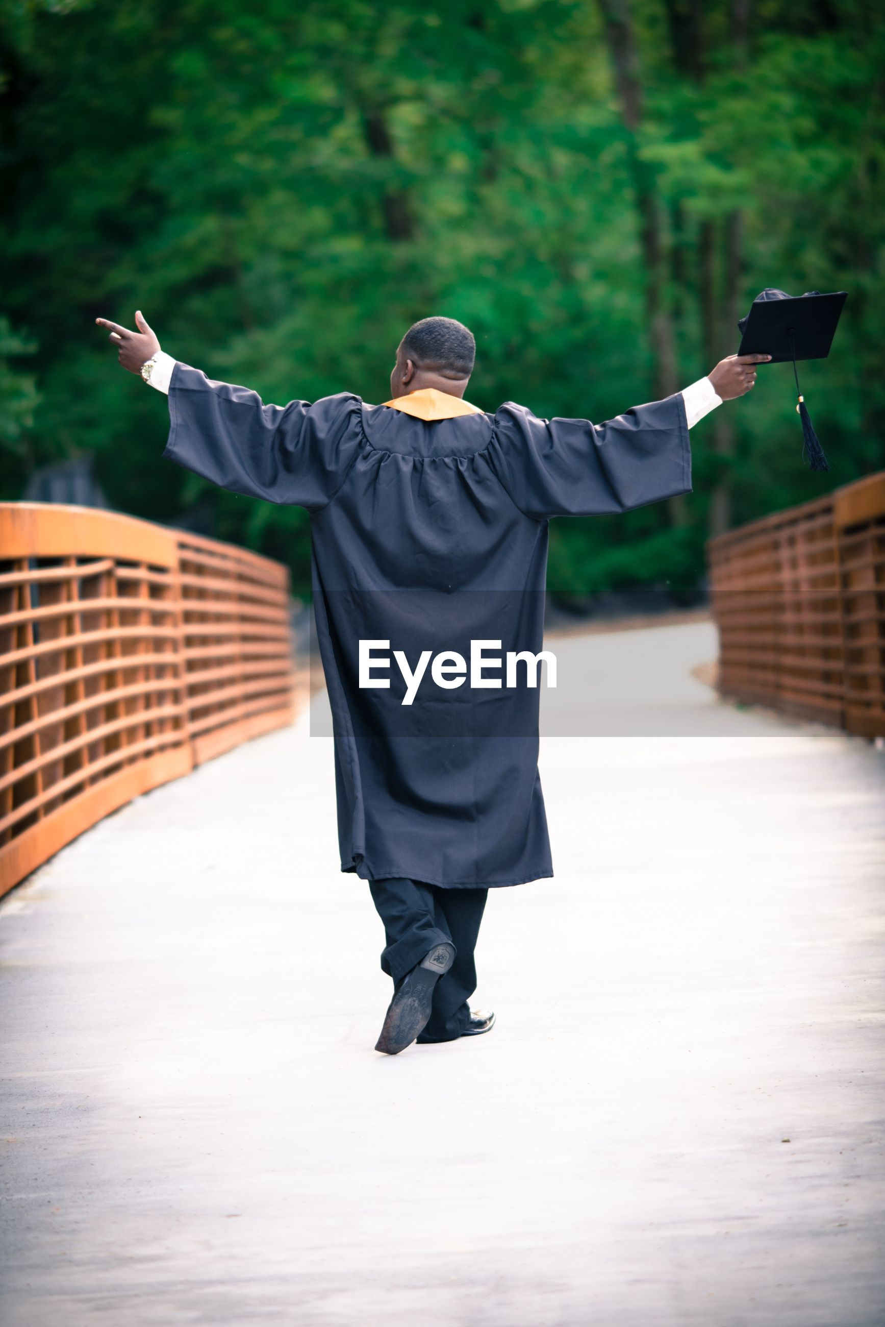 Rear view of man with arms outstretched wearing graduation gown walking on footbridge