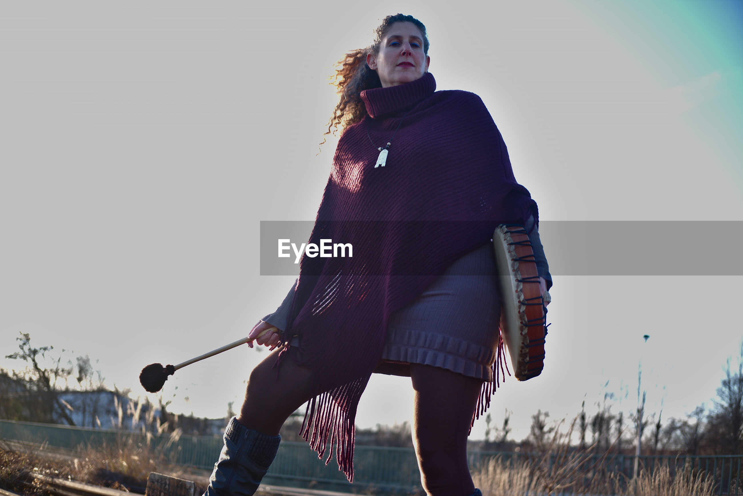 Low angle view of woman holding musical instrument standing against sky