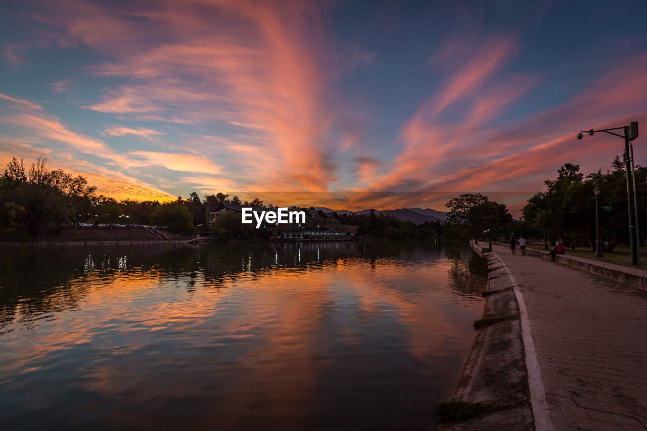 water, sky, sunset, cloud - sky, beauty in nature, reflection, scenics - nature, tranquility, nature, lake, tree, tranquil scene, orange color, no people, architecture, plant, idyllic, outdoors