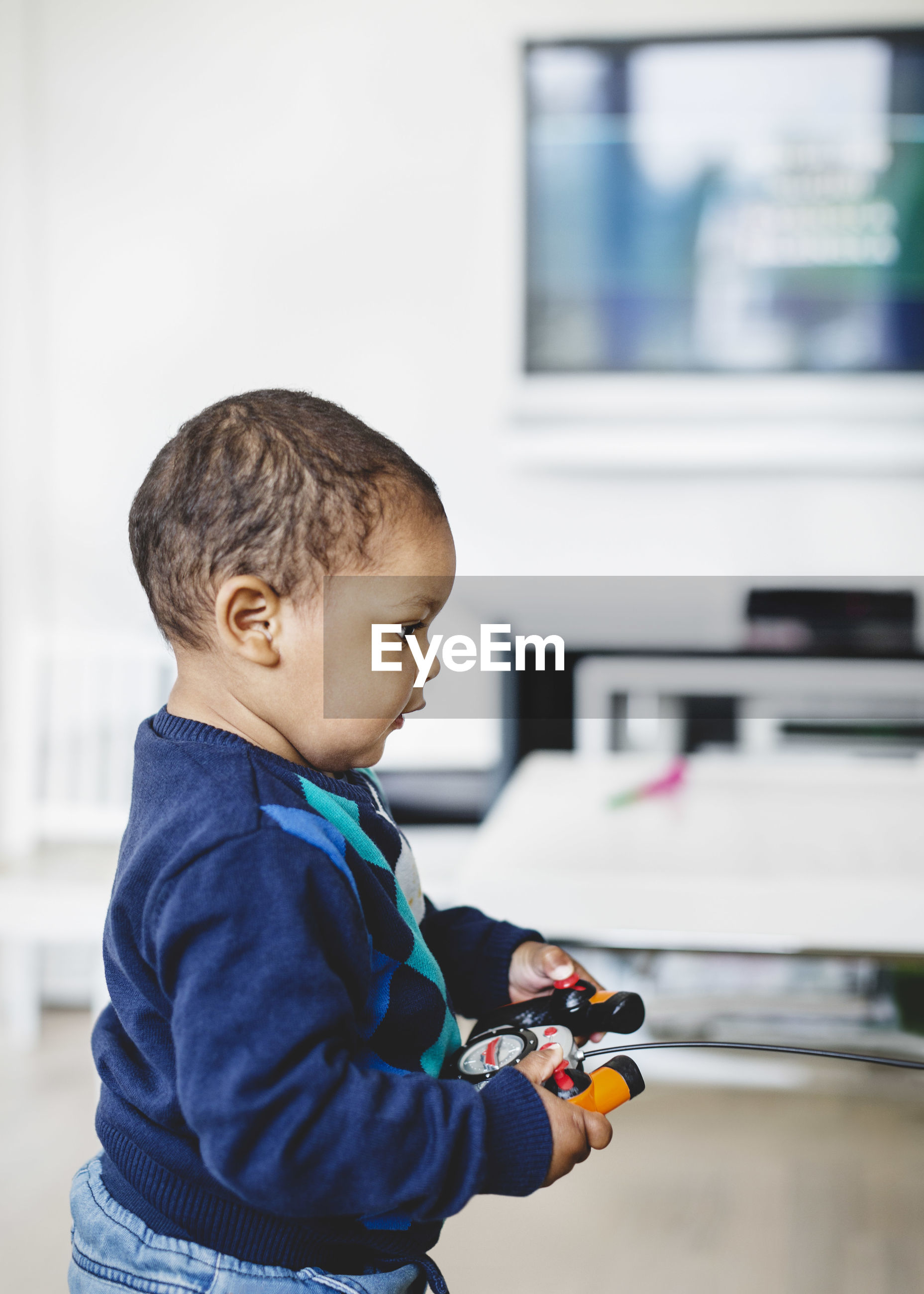 SIDE VIEW OF A BOY LOOKING AWAY WHILE HOLDING CAMERA AT HOME