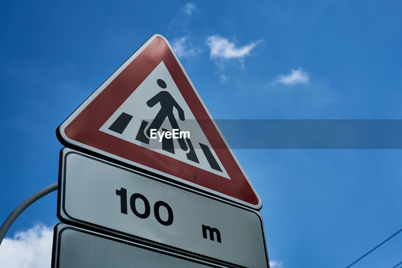 Low angle view of pedestrian crossing sign against blue sky