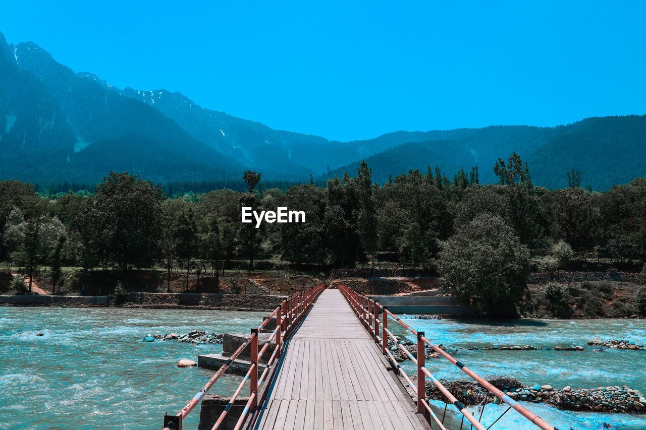 tree, water, mountain, nature, plant, scenics - nature, beauty in nature, blue, sky, tranquil scene, the way forward, tranquility, day, no people, direction, non-urban scene, built structure, wood - material, clear sky, mountain range, outdoors