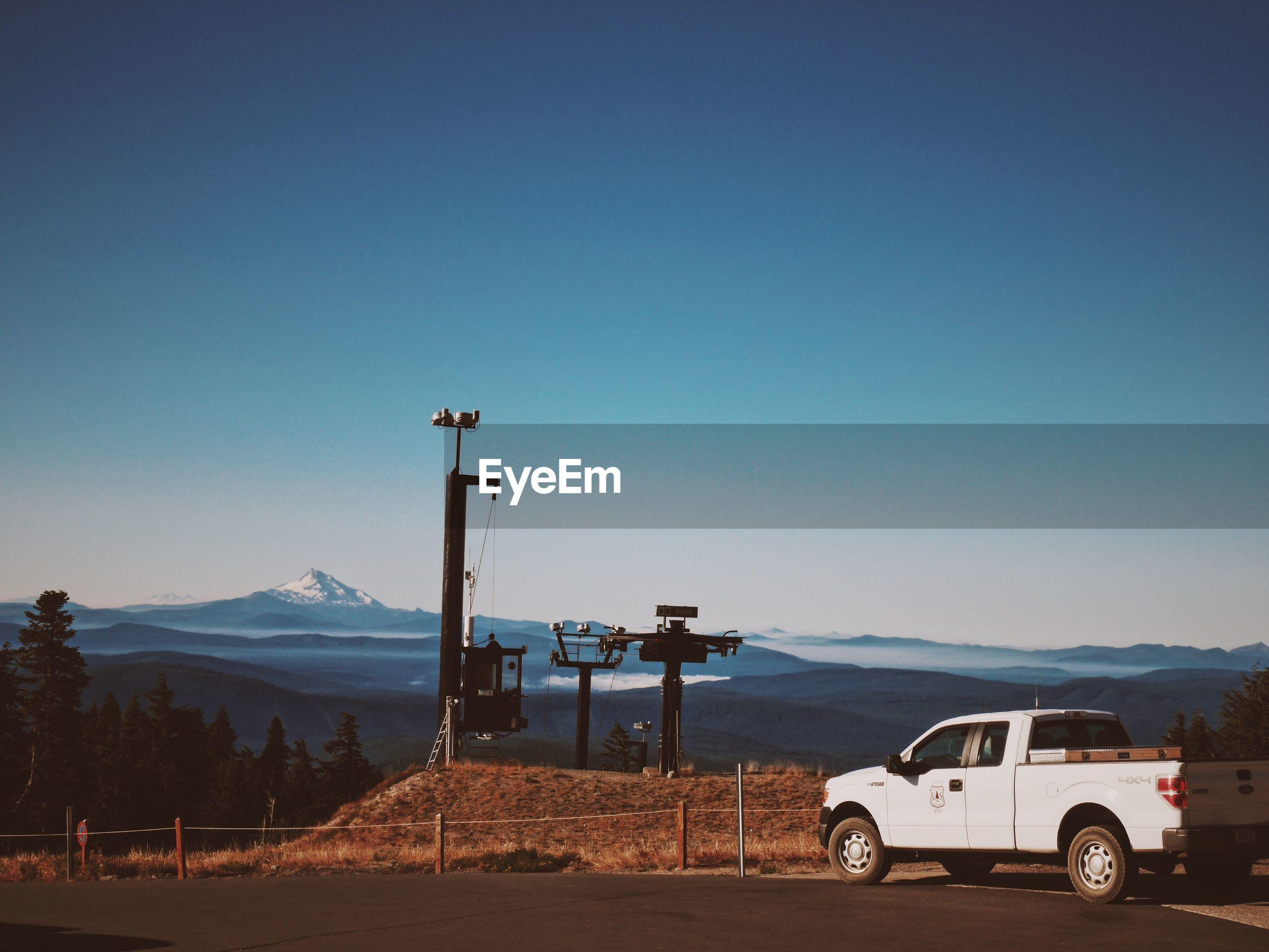 CAR ON MOUNTAIN ROAD AGAINST CLEAR BLUE SKY