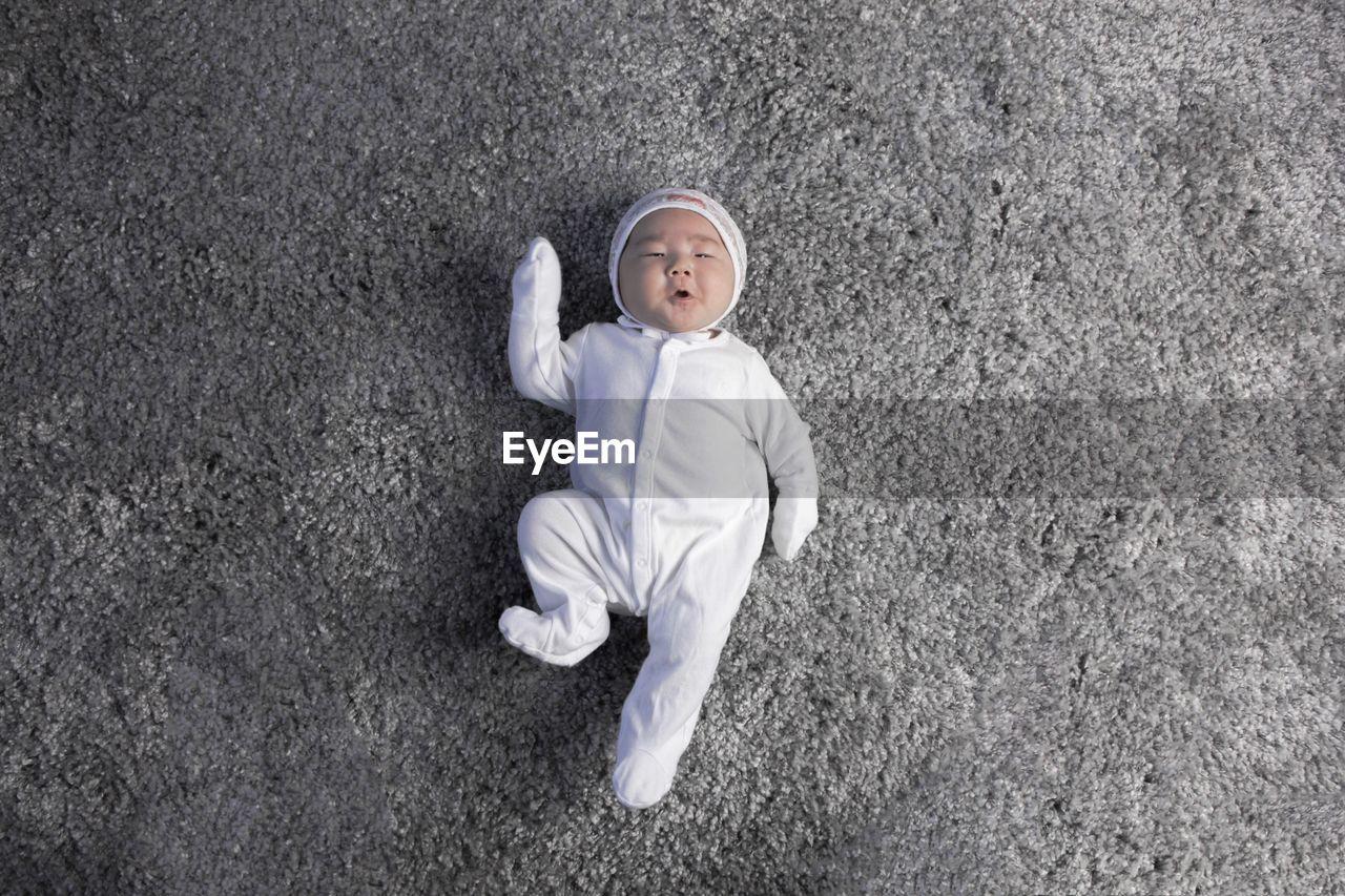 Directly above shot of baby girl lying down on rug