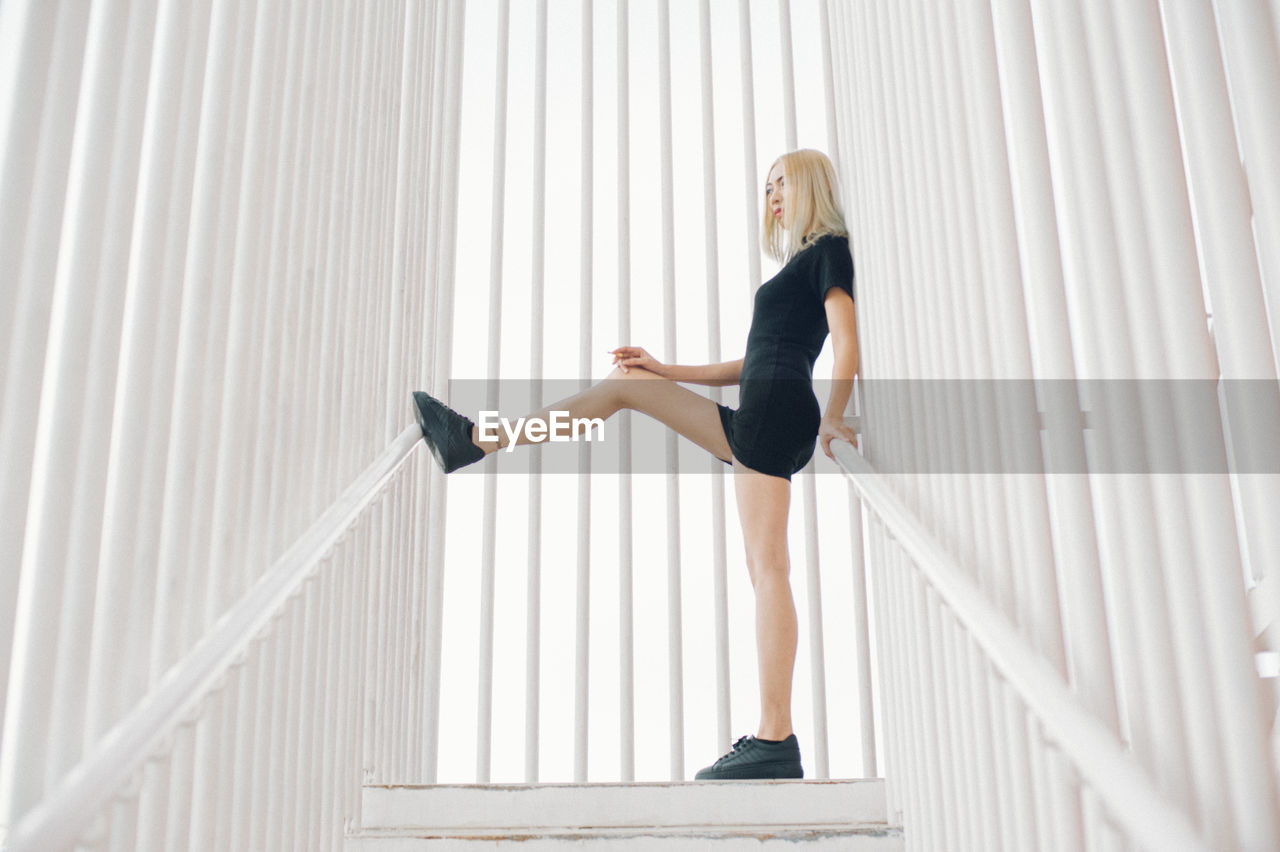 Full length of young woman standing at staircase