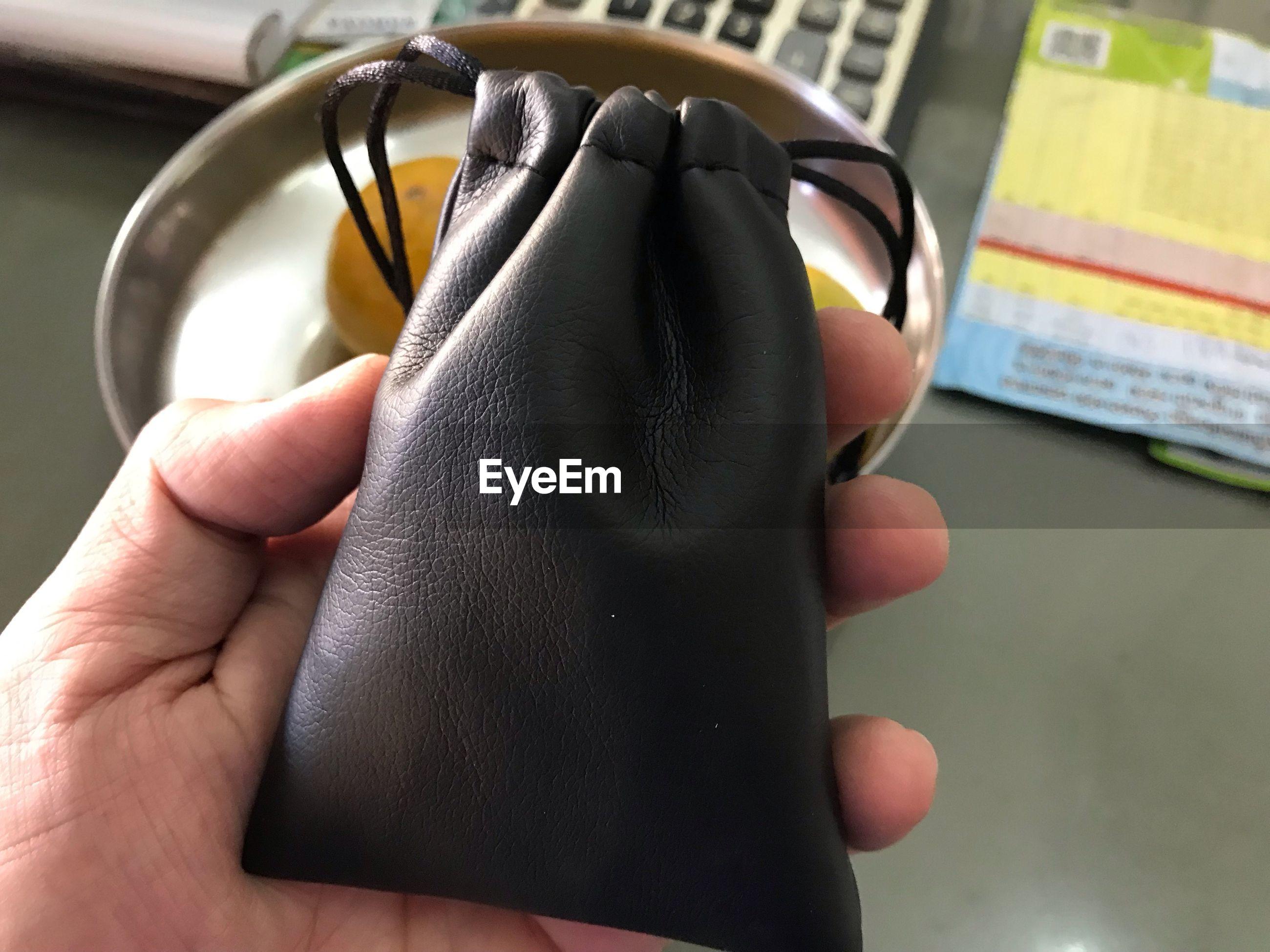 Close-up of hand holding black bag