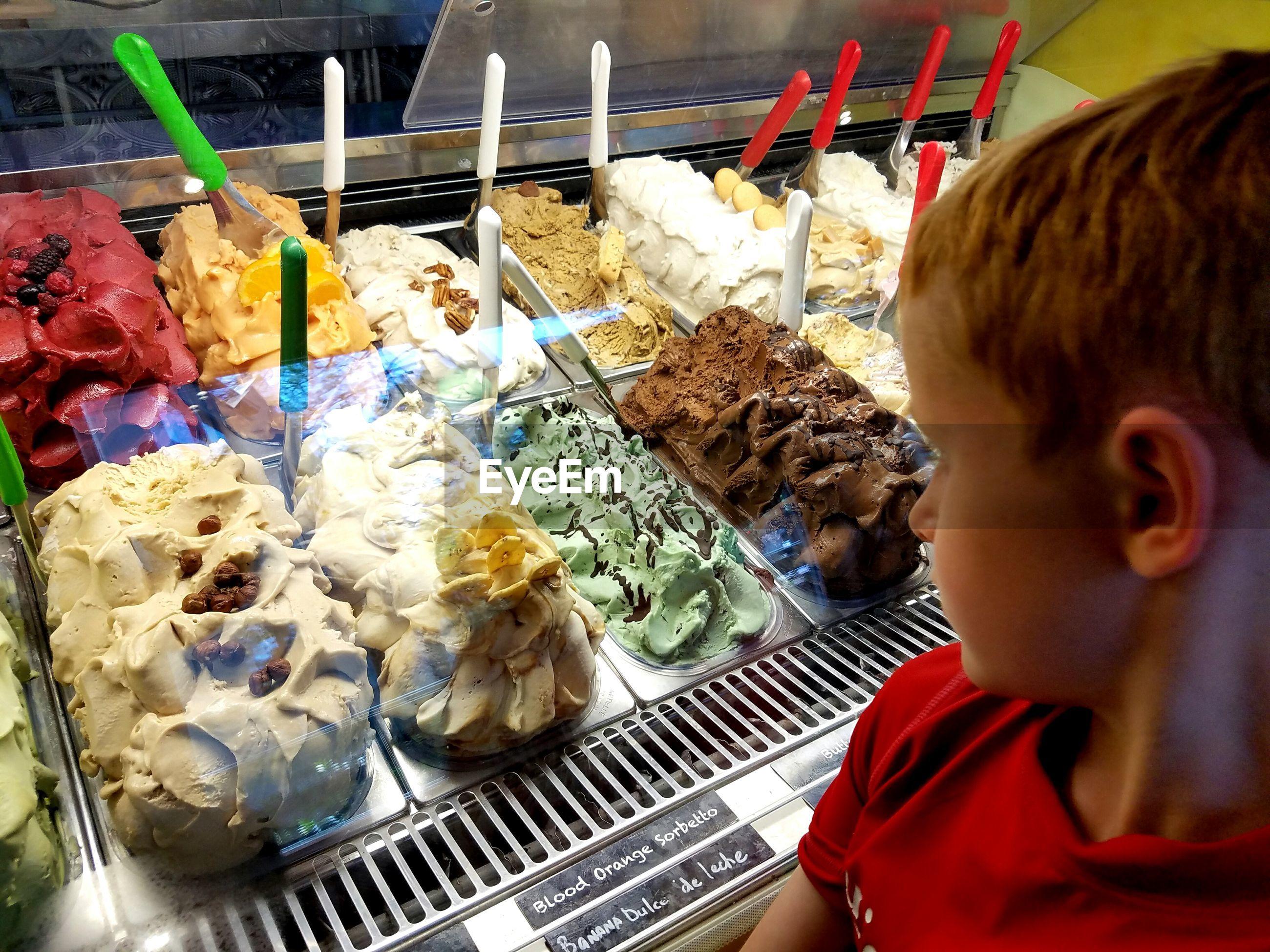 Boy looking at ice creams in ice cream parlor