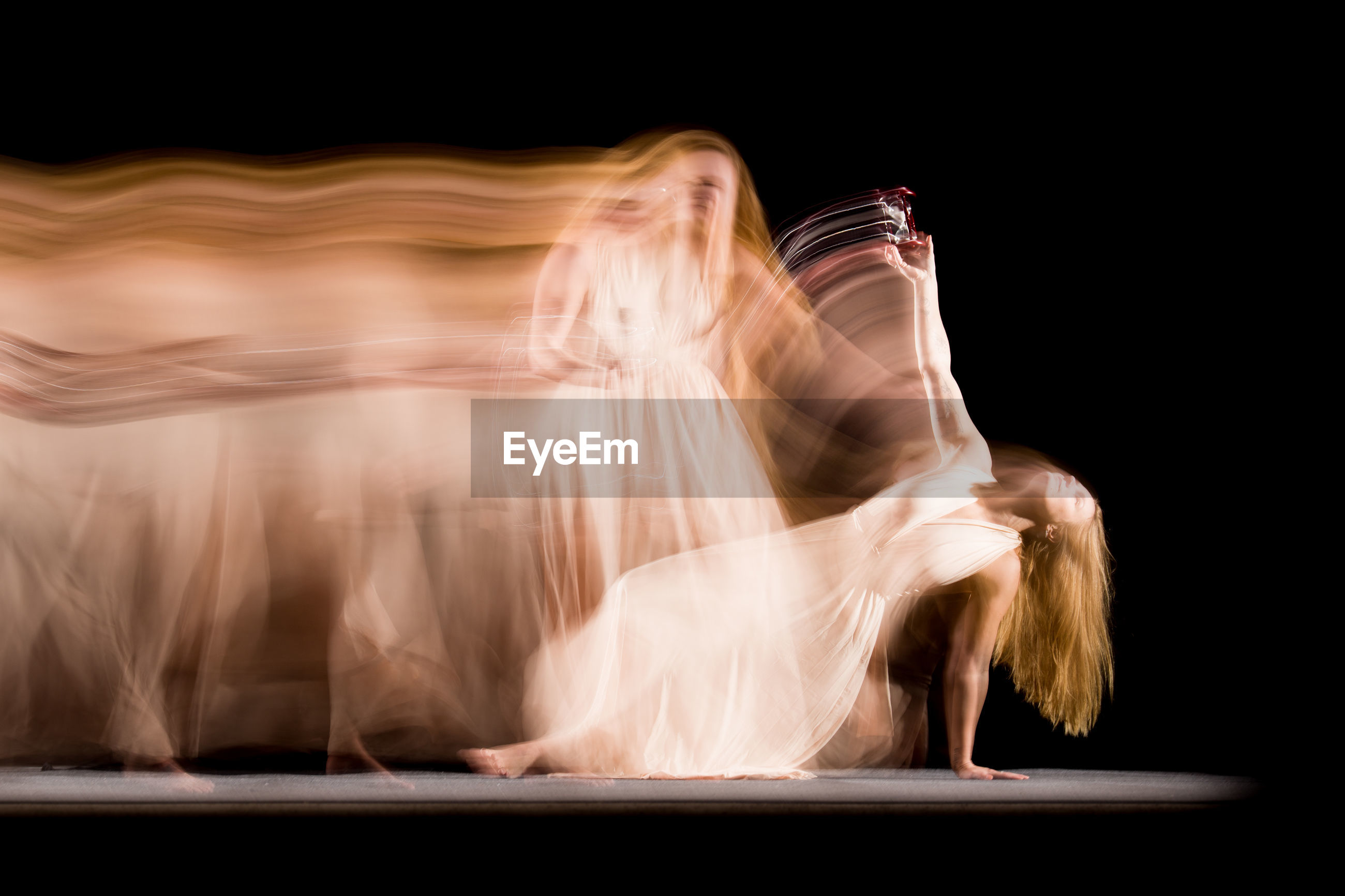 Blurred motion of woman dancing against black background
